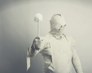 A Man Covered With Toilet Paper Holding A Toilet Brush